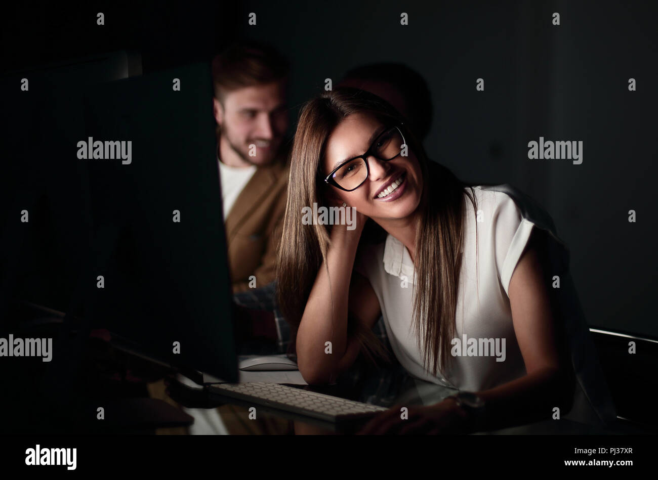 young business woman sitting at her Desk at night - Stock Image