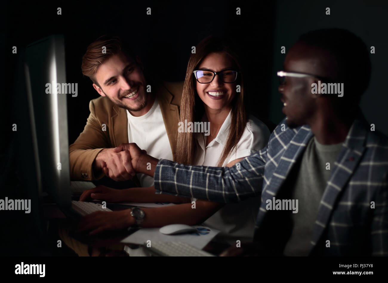 employees shake hands while sitting at the Desk - Stock Image