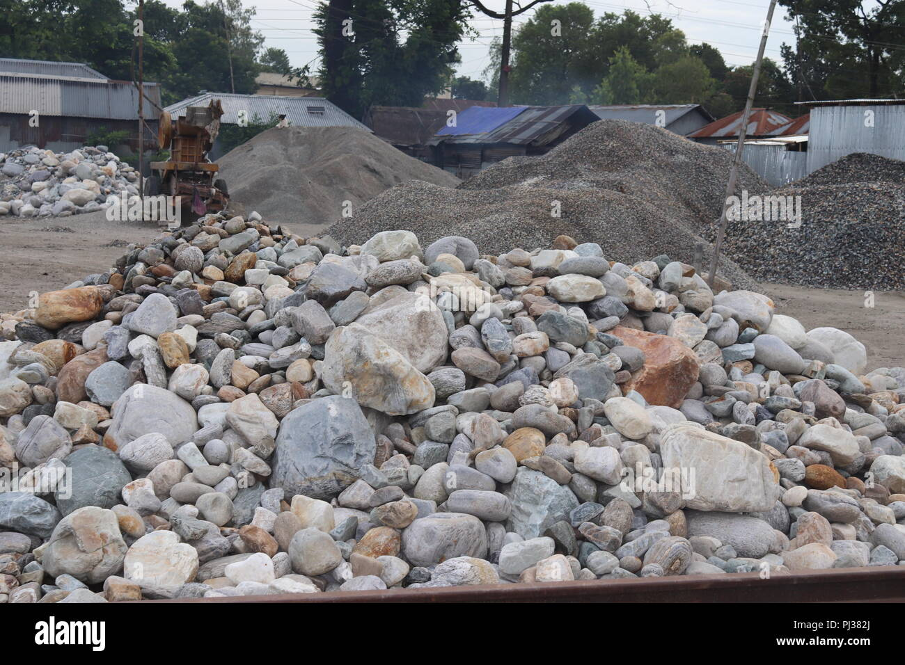 big granite stones boulders of various forms and sizes set.white stone floor in the garden.white stone wall background. - Stock Image