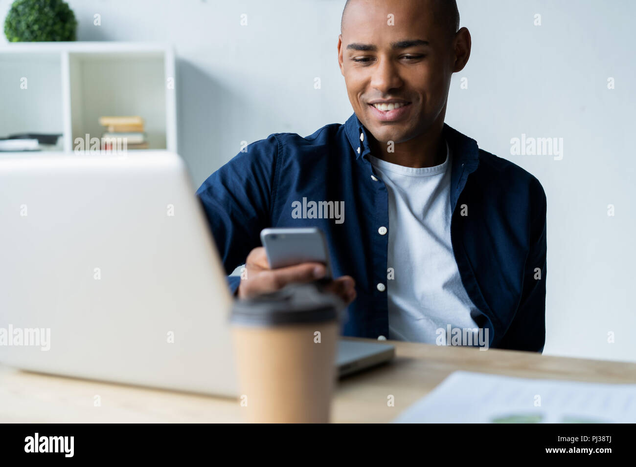 Happy african american businessman using a mobile phone in an office. Stock Photo