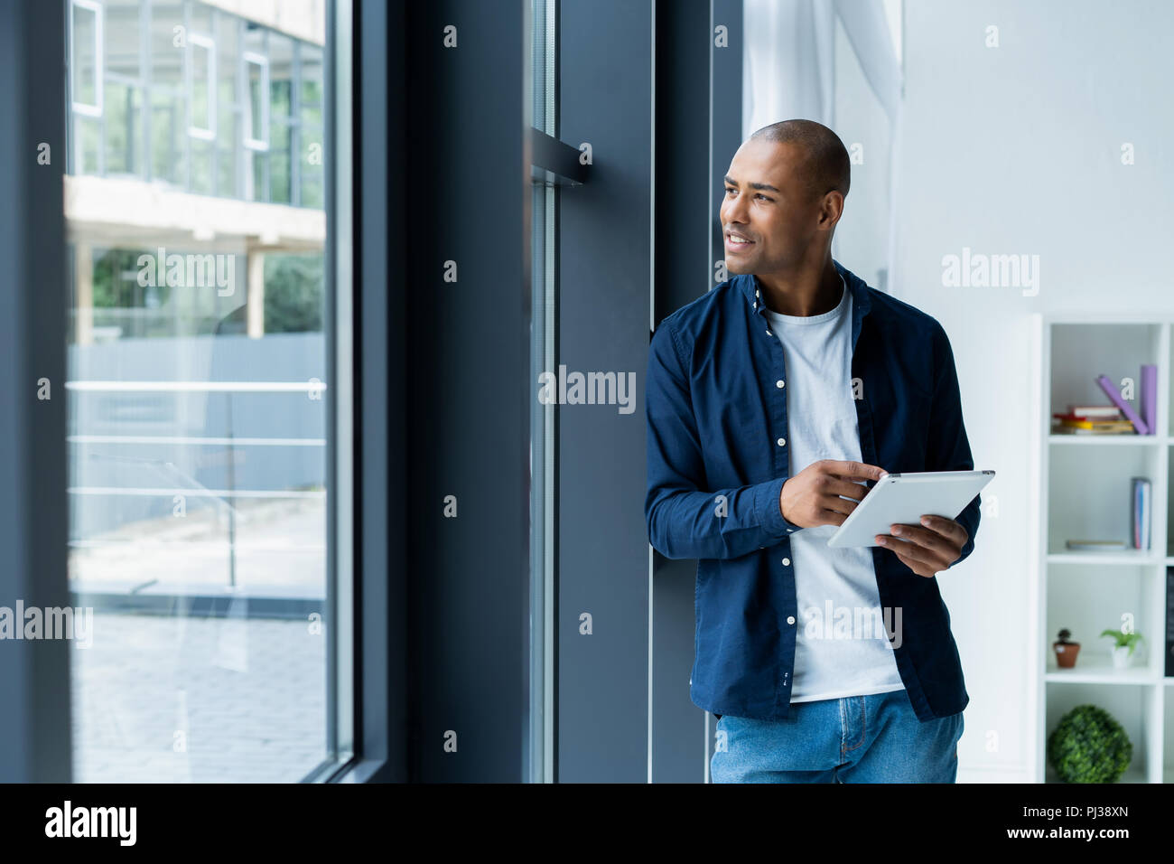 happy african american entrepreneur using tablet computer. - Stock Image