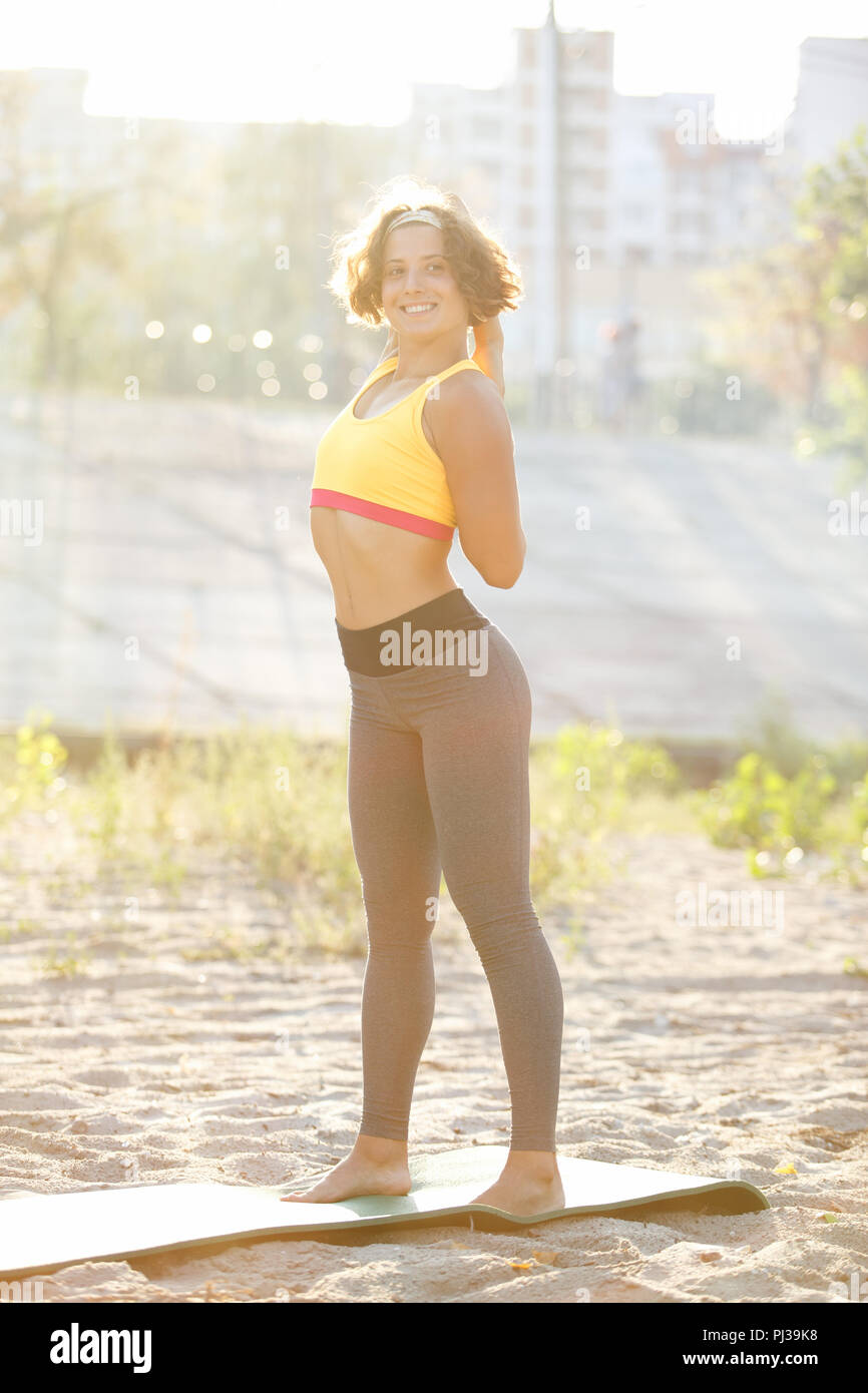 f616cbc8a3 Sporty young woman stretching outdoor on yoga mat wearing grey gym pants  and yellow sport top