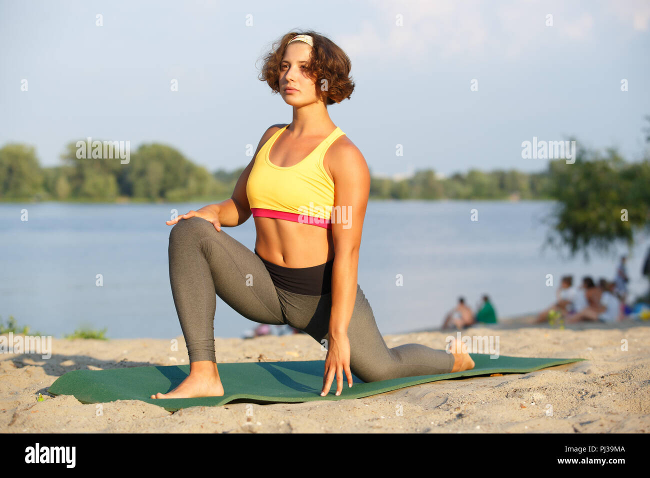 dc99b1a5f4 Pretty young girl doung yoga on mat on the beach at sunset.Beautiful white  woman