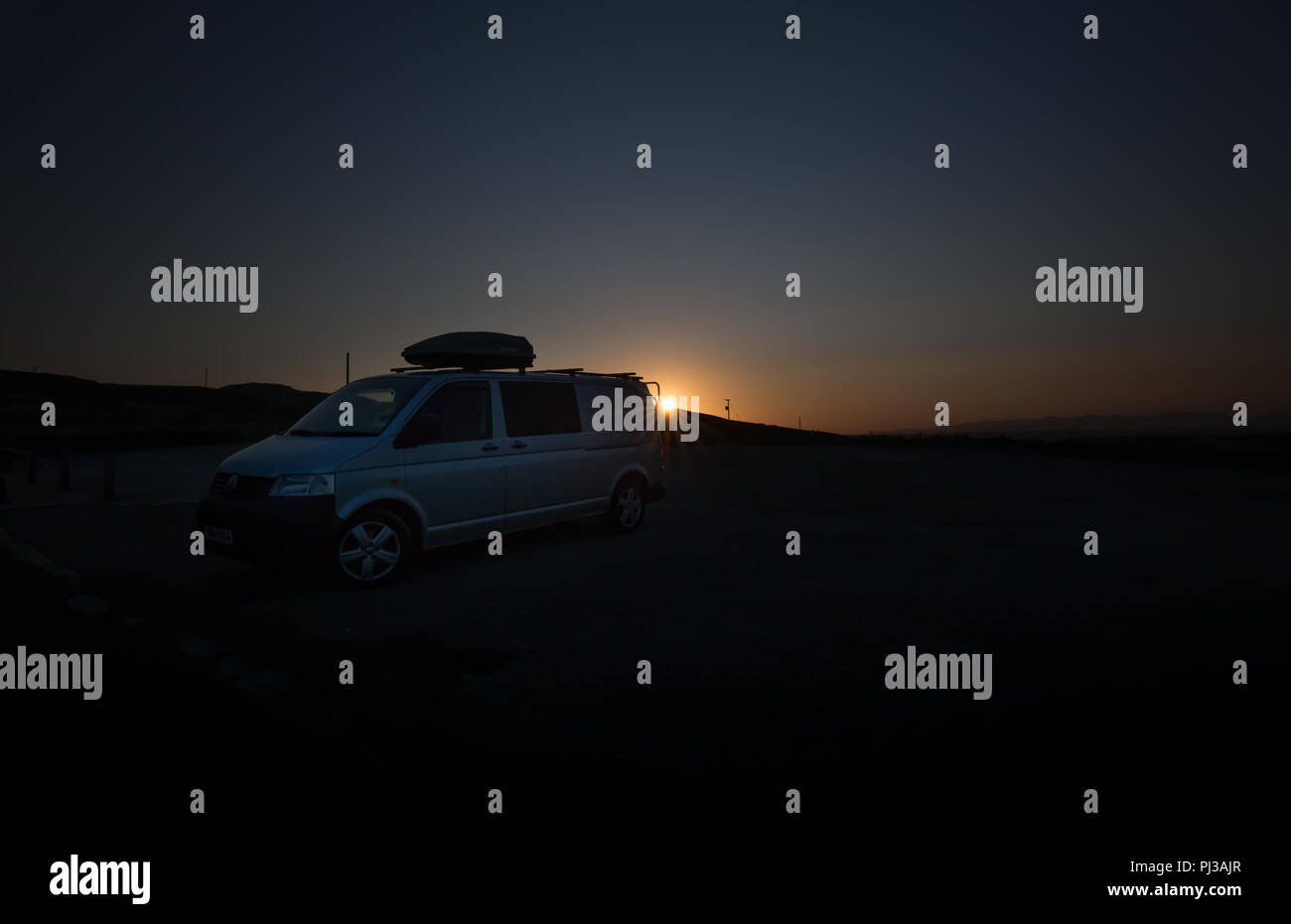 Silver VW Transporter T5 campervan (with top box) at sunrise. - Stock Image