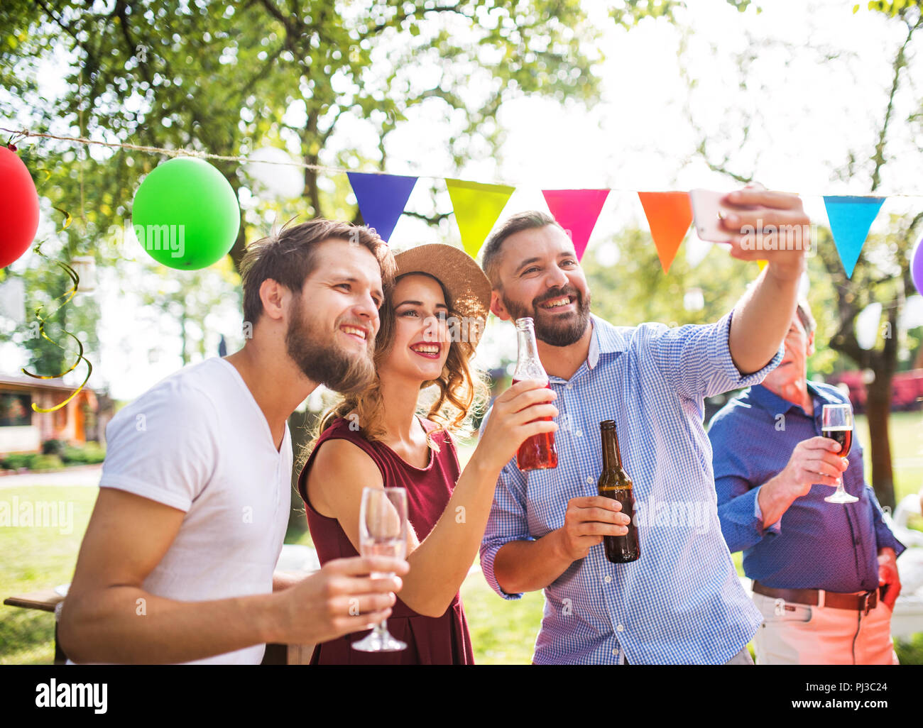 Young people taking selfie at a party outside in the backyard. - Stock Image