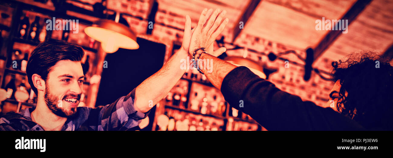 Two young men giving high five to each other - Stock Image