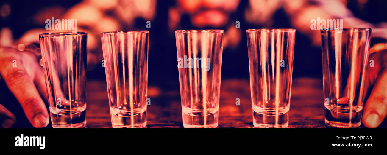Waiter placing shot glasses on counter - Stock Image