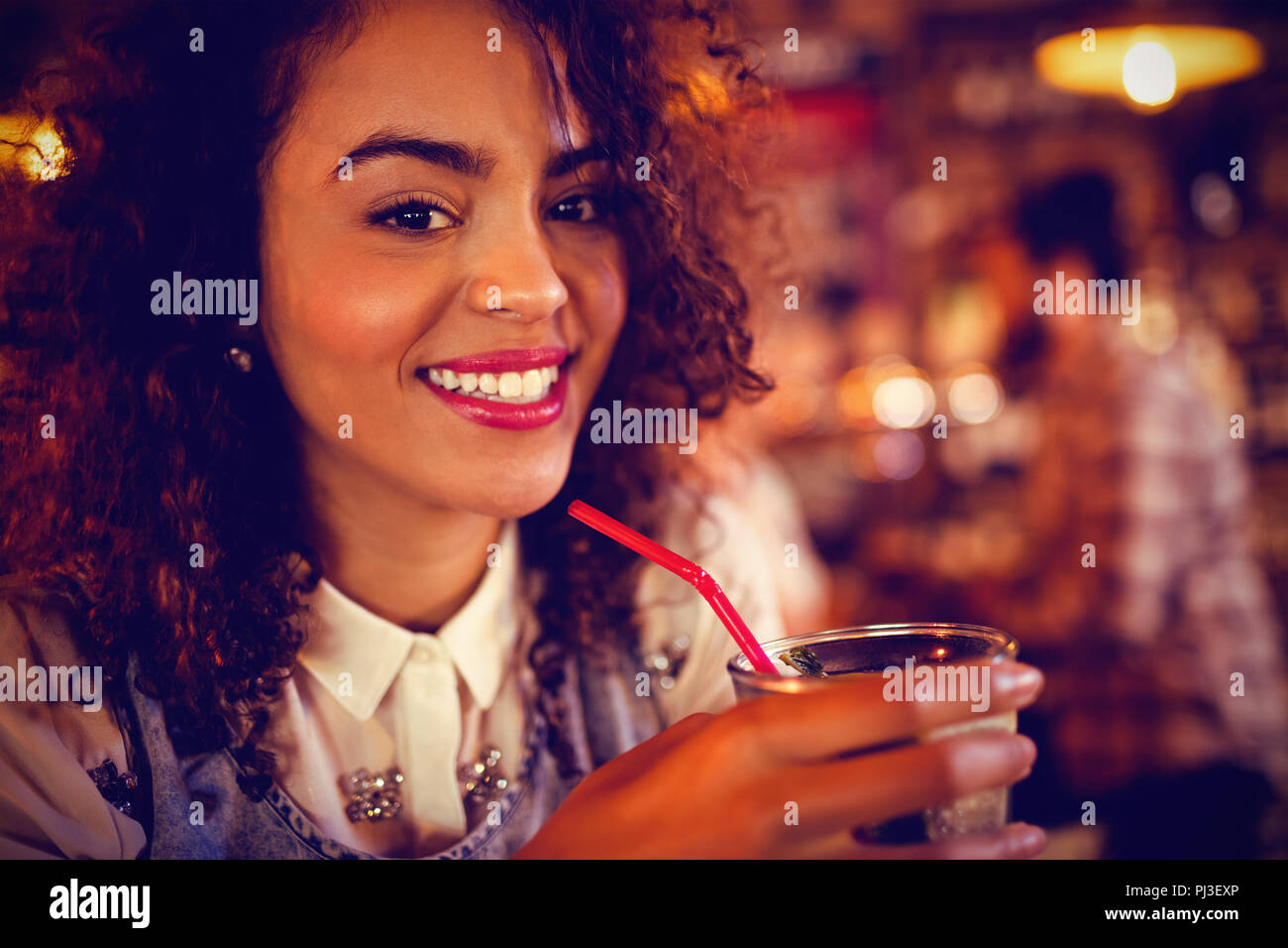 Portrait of young woman having a cocktail drink - Stock Image