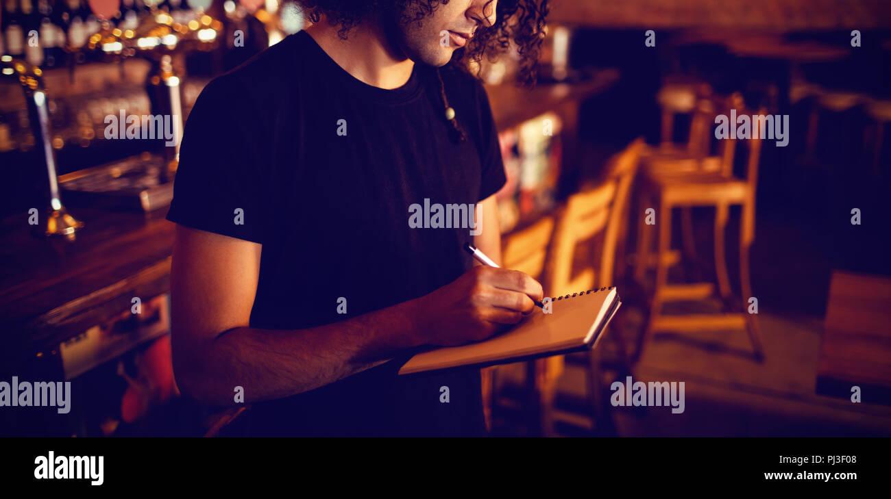 Young barman writing on diary - Stock Image