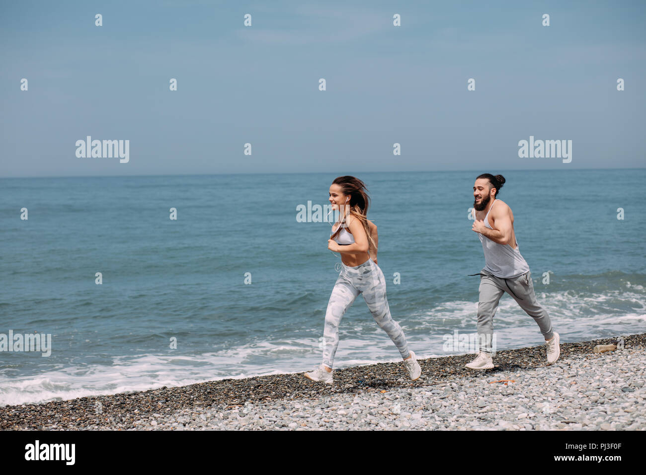 Happy couple running together beside the water at the beach - Stock Image