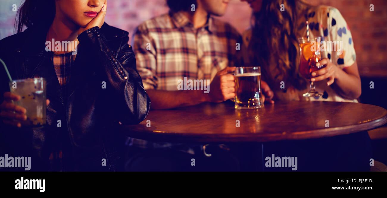 Upset woman ignoring affectionate couple - Stock Image