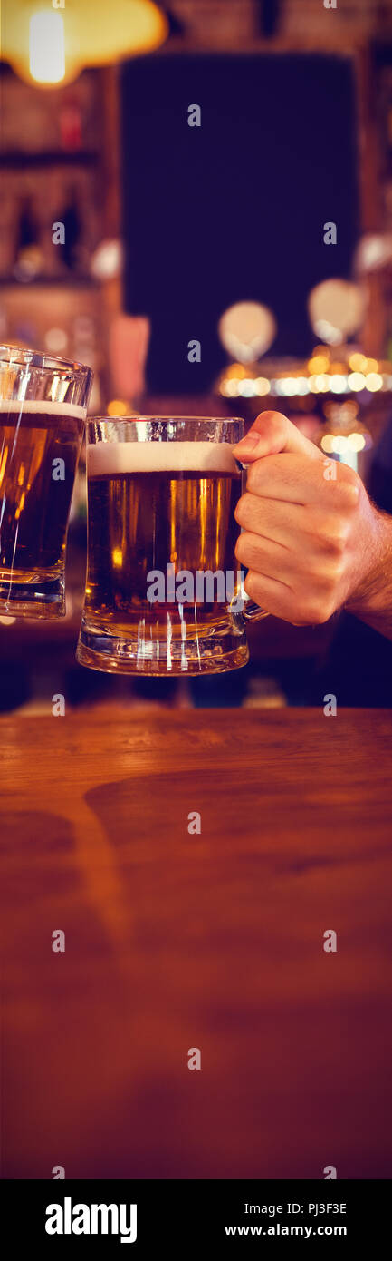 Two young men toasting their beer mugs - Stock Image