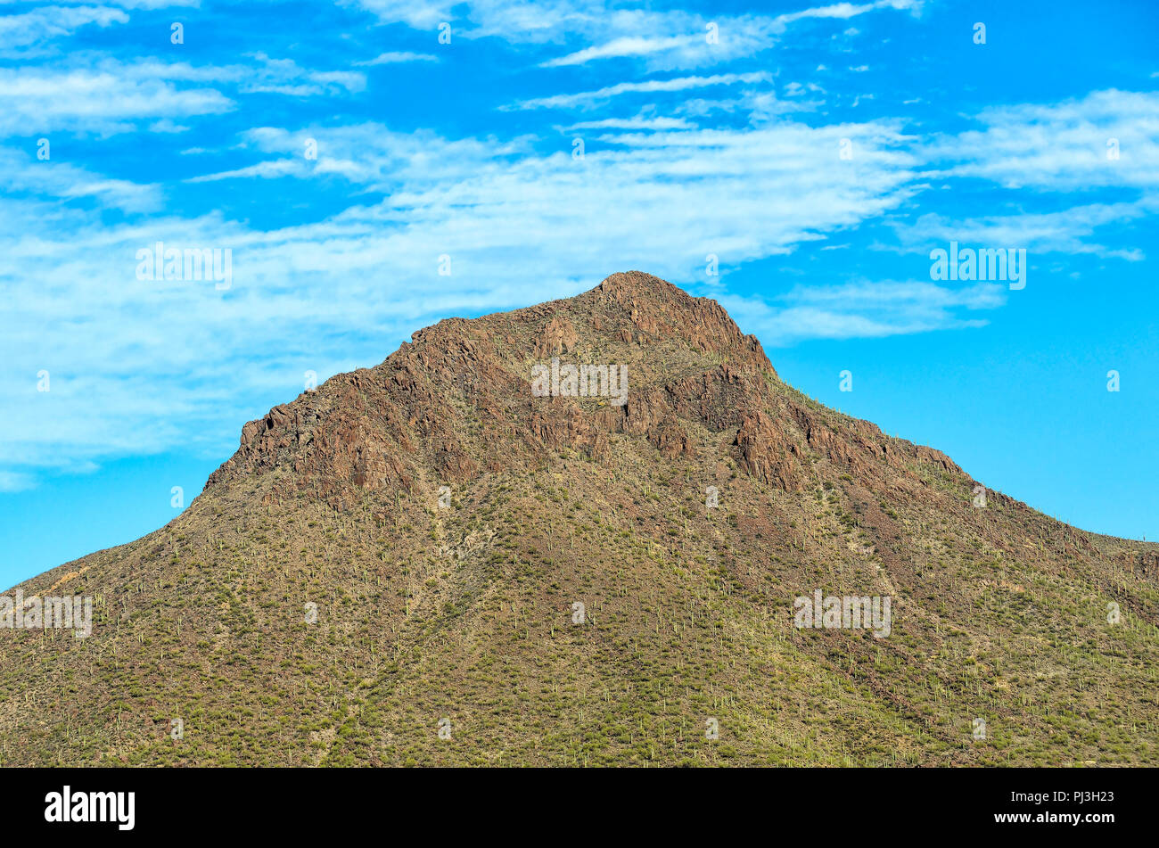 Mostly barren mountain peak under bright blue sky with fluffy white clouds. - Stock Image