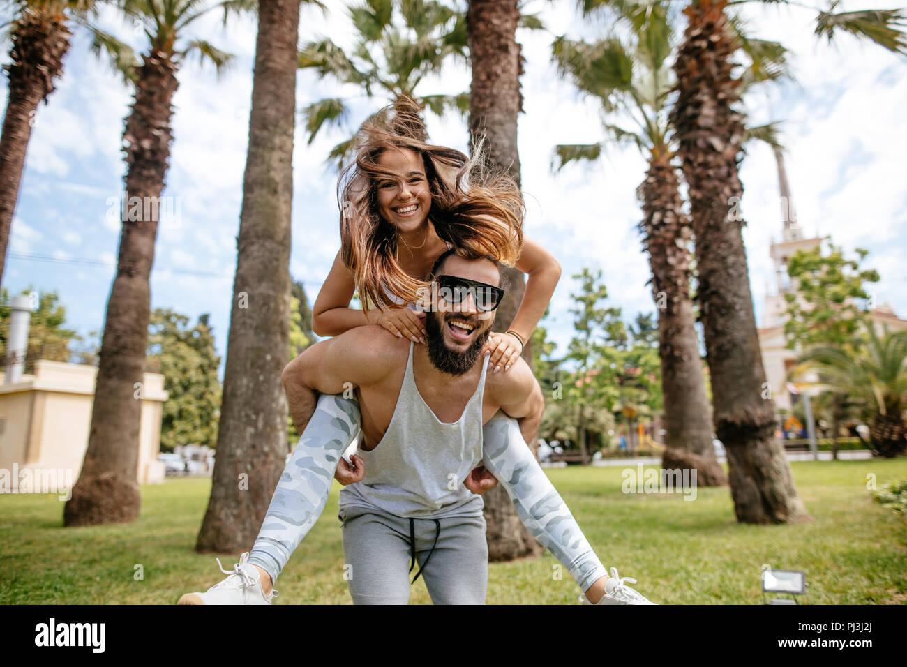 Playful sportive men giving piggyback ride to women at tropical park - Stock Image