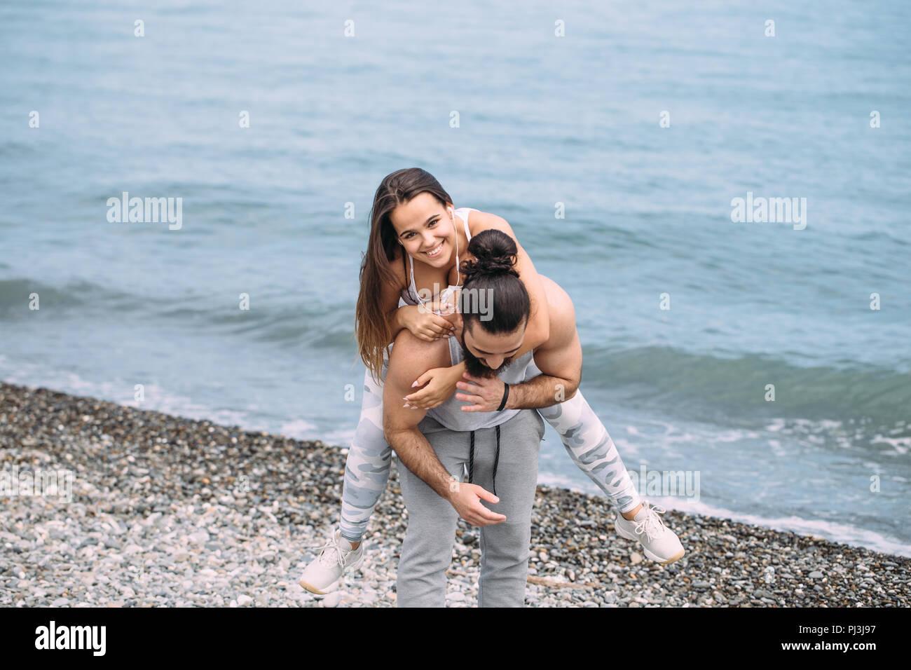 Playful sportive men giving piggyback ride to women on beach. - Stock Image