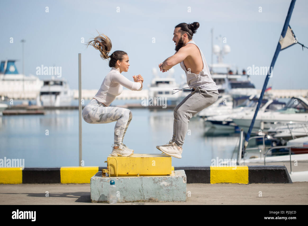 Female and male athlete is performing box jumps outdoor. - Stock Image