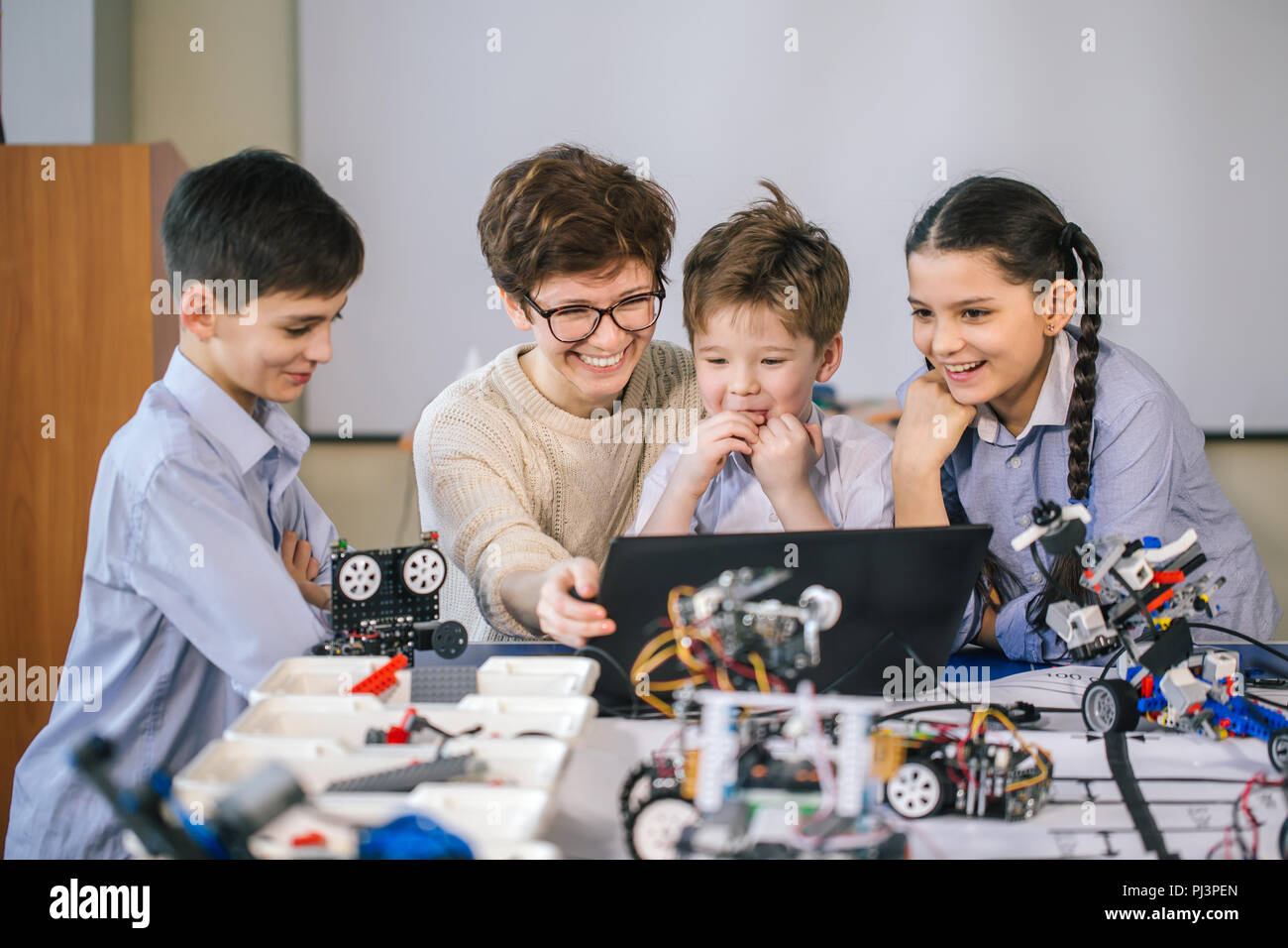 Curious children learn programming using laptops on extracurricular classes - Stock Image
