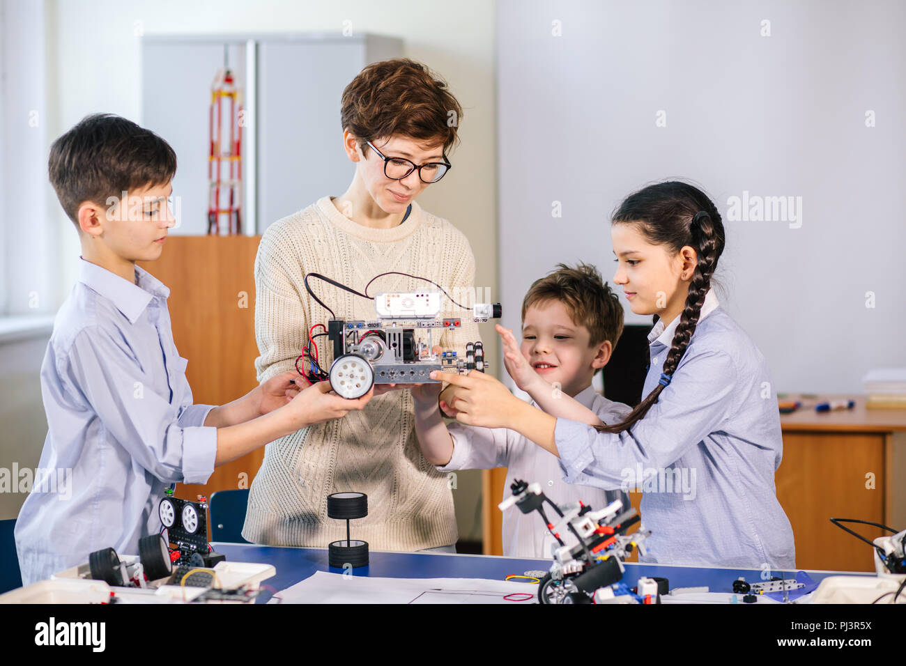 Happy children learn programming using laptops on extracurricular classes - Stock Image
