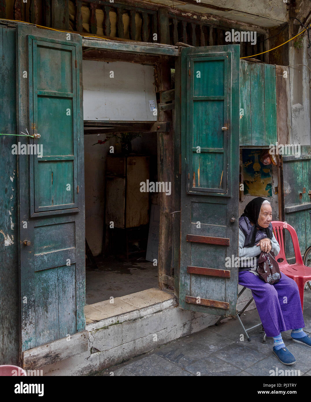 An old Asian lady sitting to the side of double green doors in Hanoi. Editorial March 26, 2017 Old Quarter Hanoi, Vietnam - Stock Image