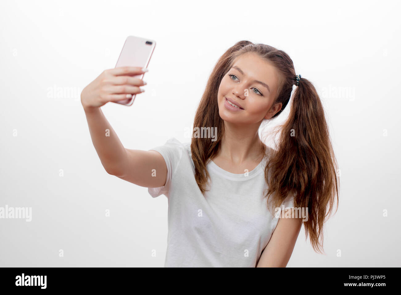attractive girl with two funny ponytails taking picture of herself, - Stock Image
