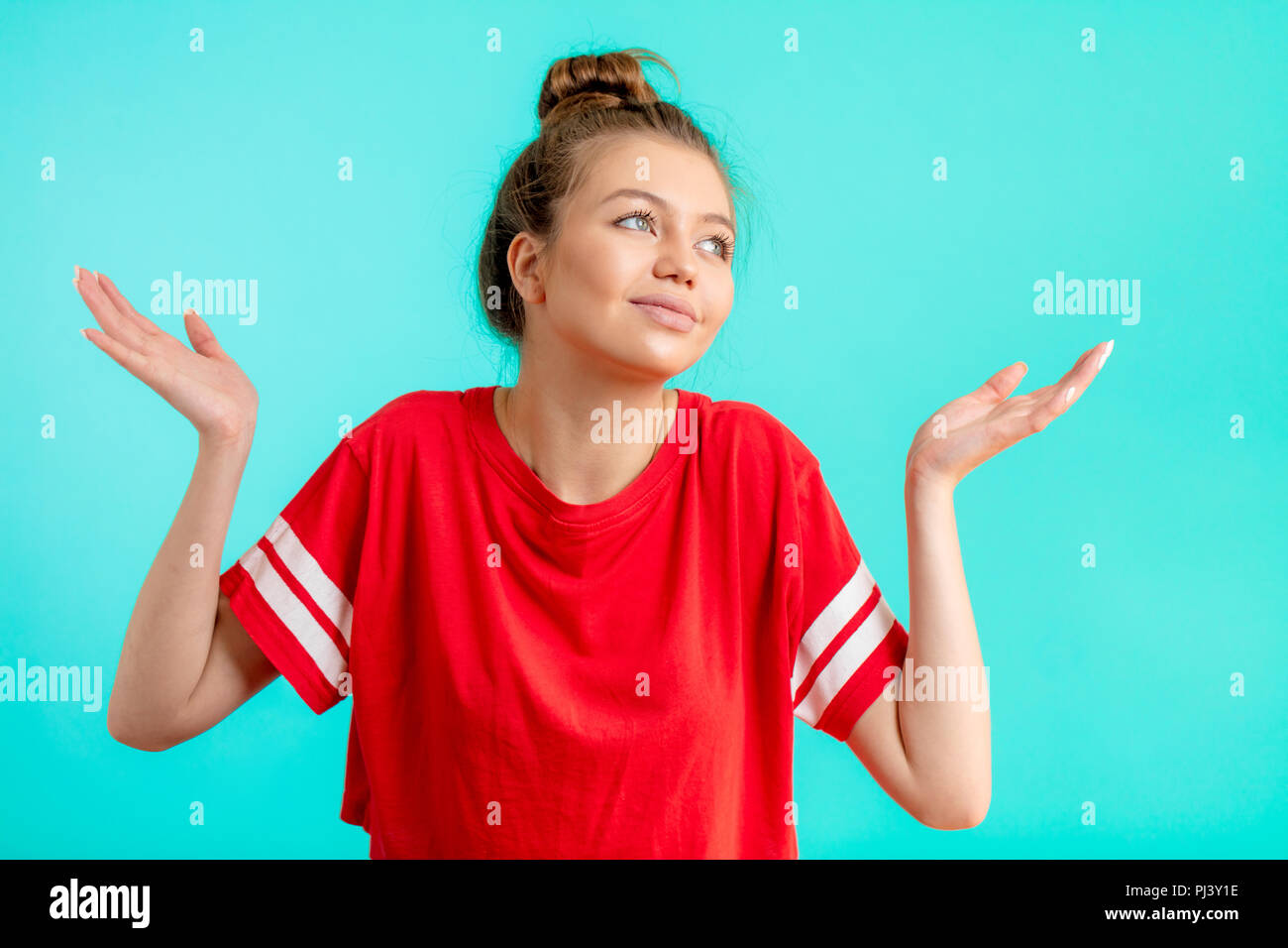 young confused woman in fashion red t-shirt with arms out shrugs shoulders - Stock Image