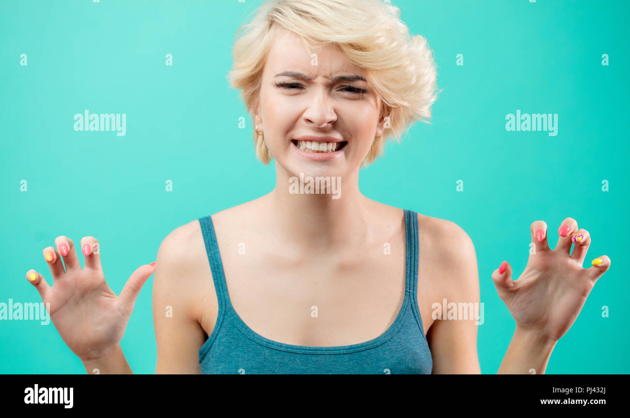close up portrait of young angry woman with clenched teeth on blue background - Stock Image