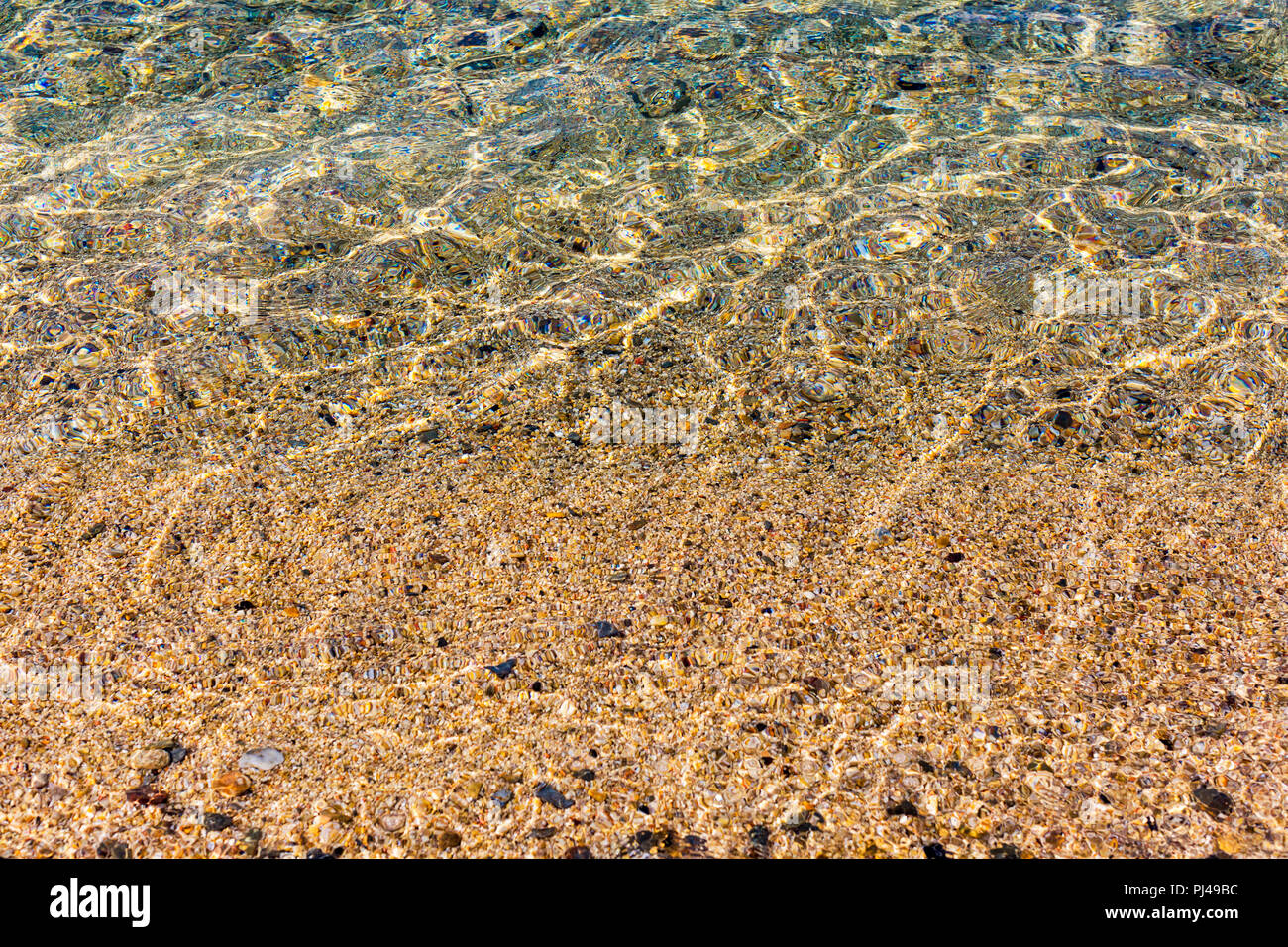 Background of transparent clear water of sea, iridescent sunlight reflecting on sea bottom - Stock Image