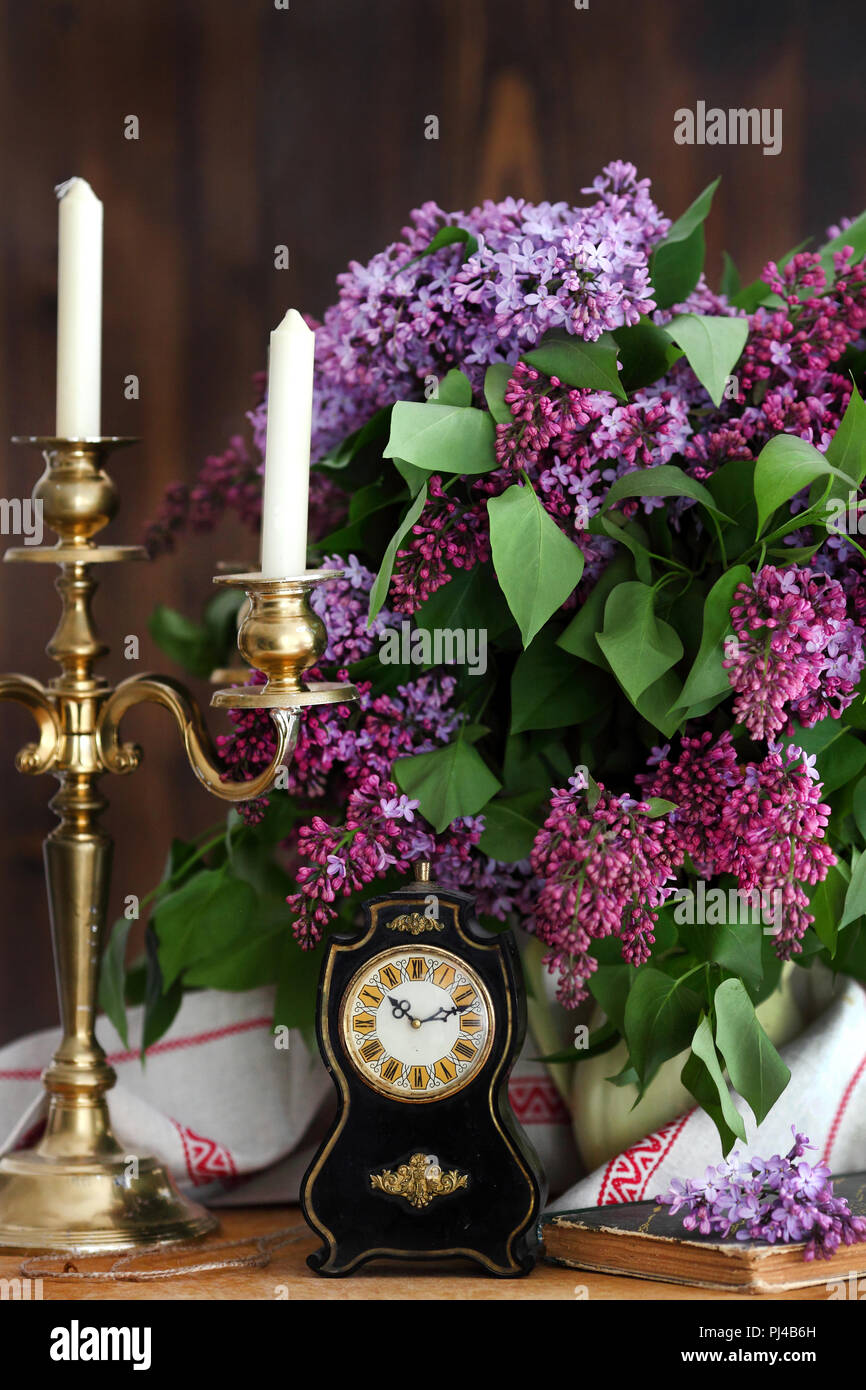 Lilac bouquet in ceramic jug, lilac brush and forging candle holder with candles. Still life. - Stock Image