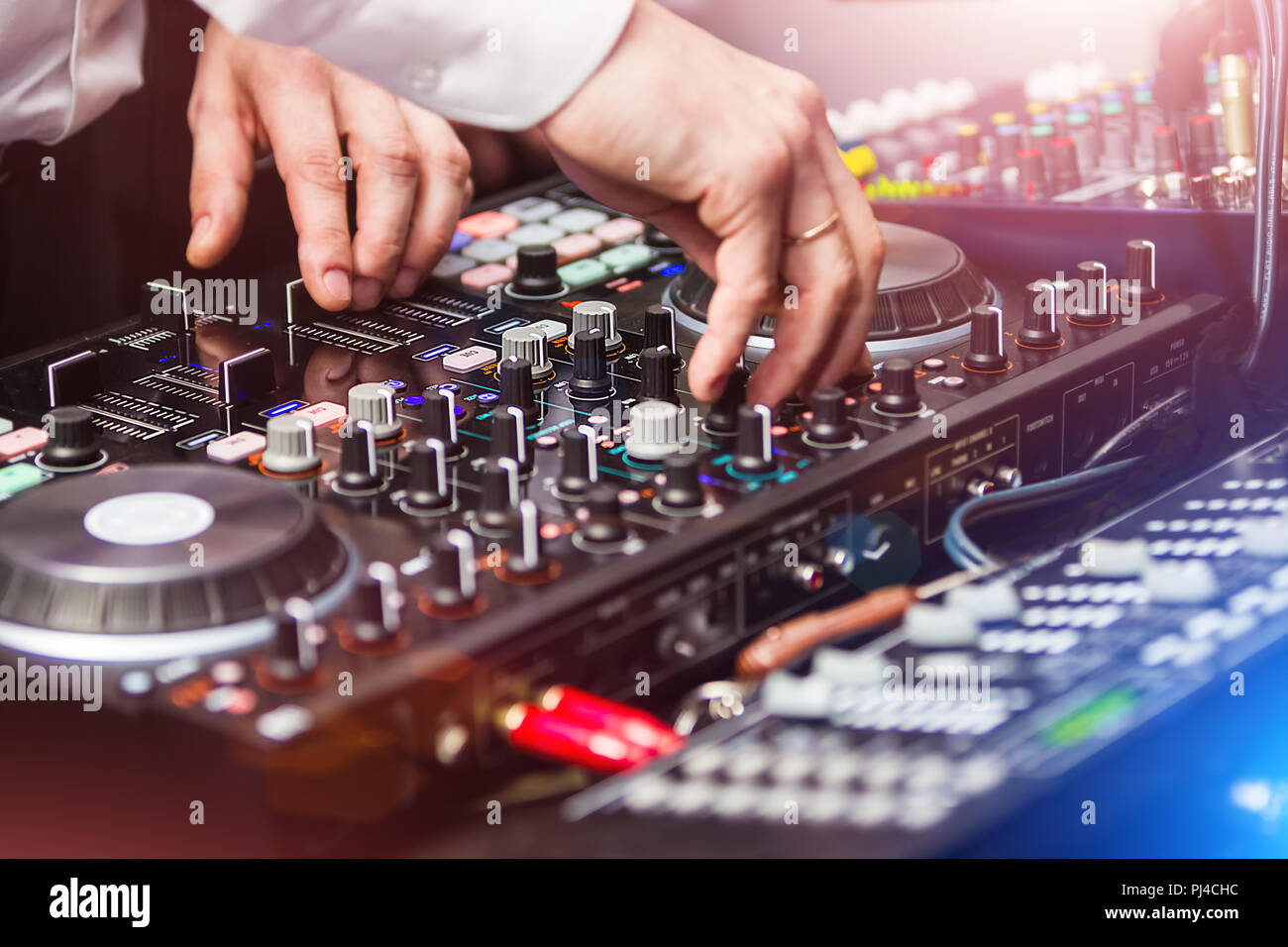 DJ playing music at control panel - Stock Image