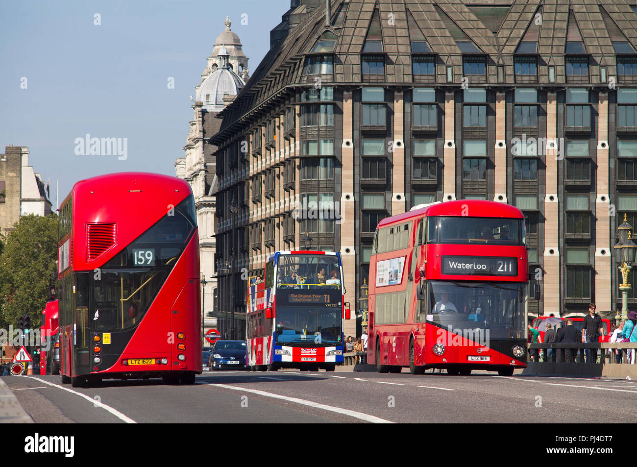 A pair of New Routemaster red double decker London buses passing each other on Westminster Bridge. - Stock Image