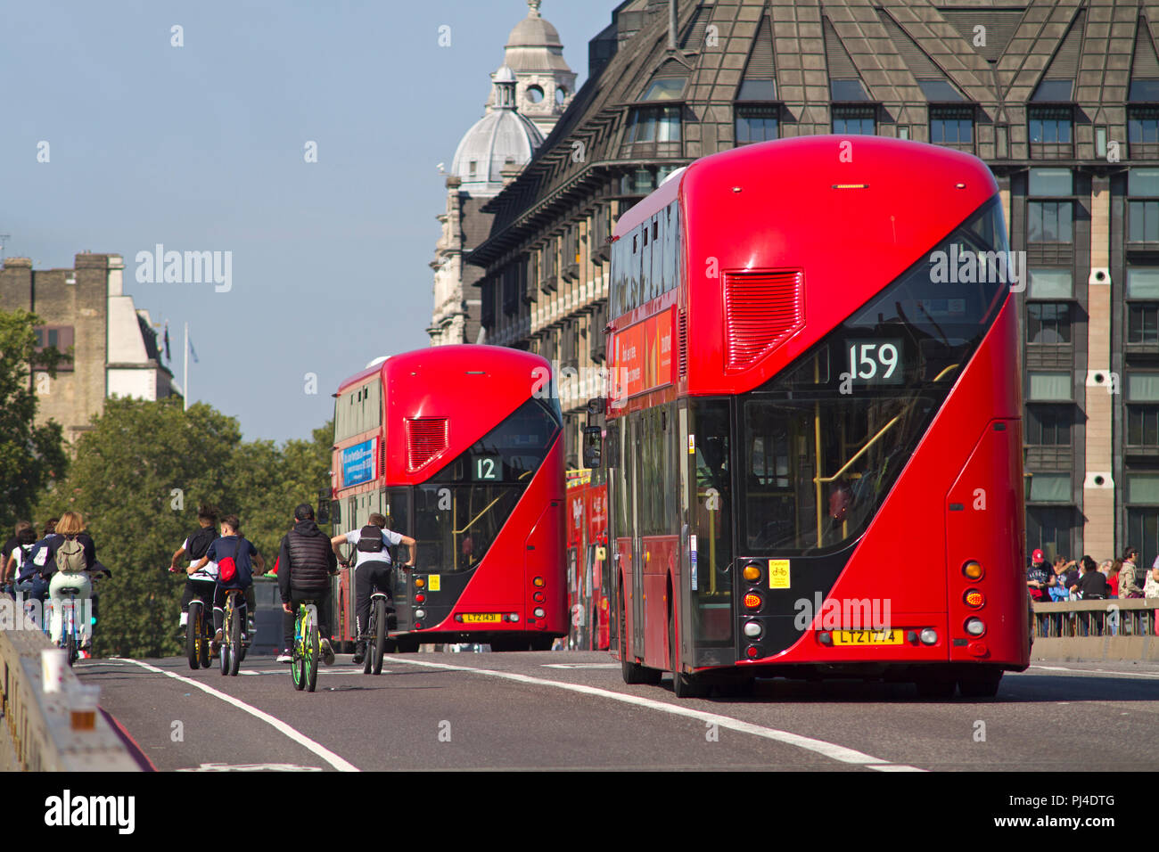Rear view of a pair of New Routemaster red double decker London buses passing some cyclists on Westminster Bridge. - Stock Image