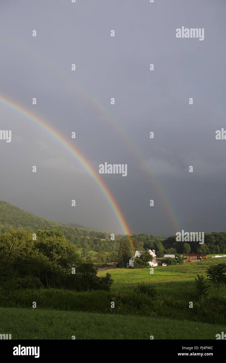 double rainbow over a farm mountain - Stock Image