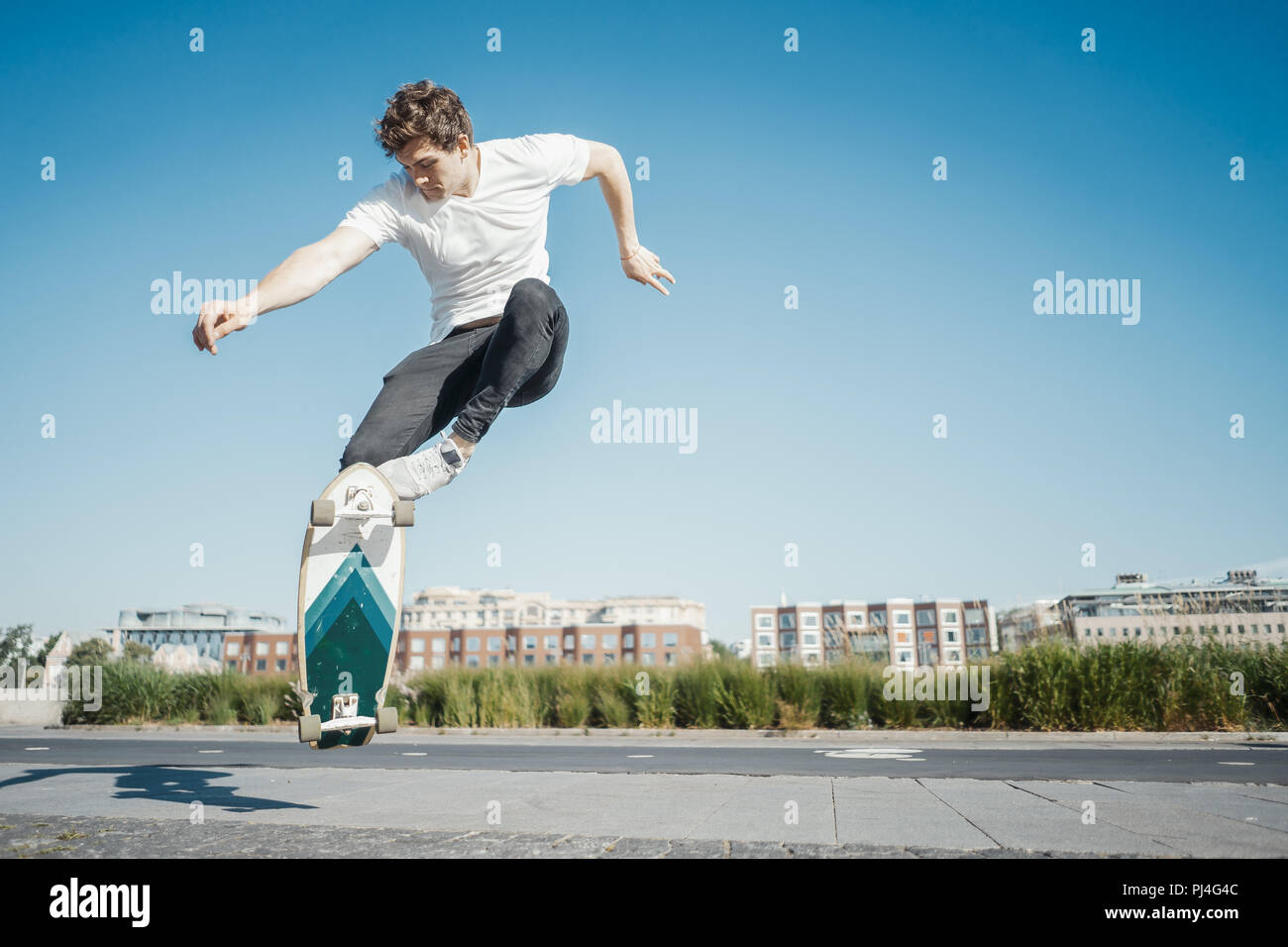 Young attractive man riding and jumping longboard in the park. - Stock Image