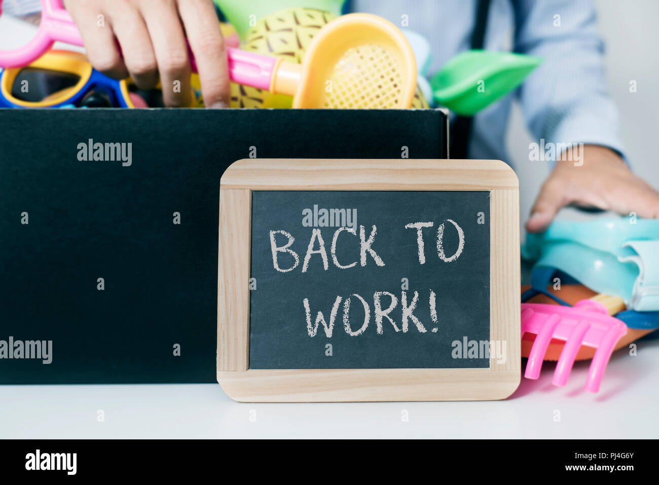 closeup of a caucasian man, at his office desk, storing in a box some summer stuff, such as different toy shovels, rakes and buckets, and a blackboard - Stock Image
