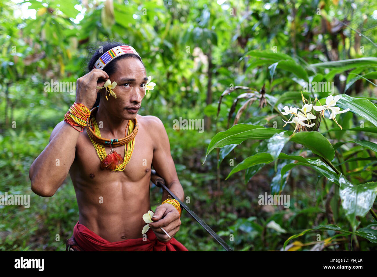 Portrait of the youngest shaman, smiling and decorated with flowers - Stock Image