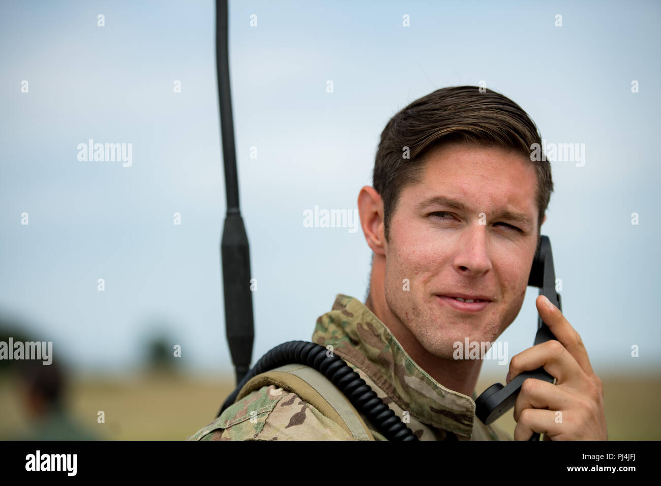 U.S. Air Force Tech. Sgt. Craig Reinwald, 435th Contingency Response Squadron contingency air traffic controller, listens to his radio at Boboc Air Base, Romania, Aug. 23, 2018. Reinwald and his team provided ground support for the 37th Airlift Squadron pilots dropping Romanian air force paratroopers out of C-130J Super Hercules aircraft as part of exercise Carpathian Summer 2018. (U.S. Air Force photo by Senior Airman Devin Boyer) Stock Photo