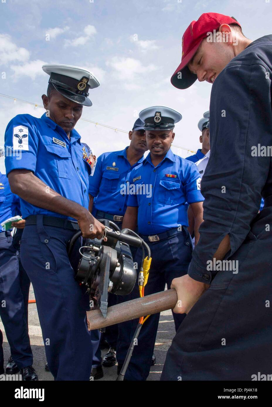 180826-N-PH222-0037 TRINCOMALEE, SRI LANKA (August 26, 2018) Damage Controlman 3rd Class Wayne L. Batten, from Elizabeth W.Va., conducts training on damage control equipment with Sri Lanka navy sailors on the flight deck of San Antonio-class amphibious transport dock USS Anchorage (LPD 23) during a regularly scheduled deployment of the Essex Amphibious Ready Group (ARG) and the 13th Marine Expeditionary Unit (MEU). Anchorage and the embarked Marines of the 13th MEU are conducting a theater security cooperation exercise with the Sri Lankan navy and Marines. Part of a growing U.S.-Sri Lanka nava - Stock Image