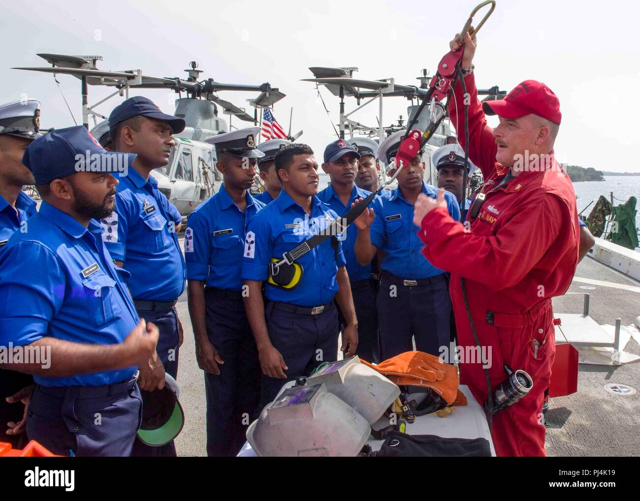 180826-N-PH222-0044 TRINCOMALEE, SRI LANKA (August 26, 2018) Senior Chief Damage Controlman, from Roanoke Rapids, N.C., conducts training on damage control equipment with Sri Lanka navy sailors on the flight deck of San Antonio-class amphibious transport dock USS Anchorage (LPD 23) during a regularly scheduled deployment of the Essex Amphibious Ready Group (ARG) and the 13th Marine Expeditionary Unit (MEU). Anchorage and the embarked Marines of the 13th MEU are conducting a theater security cooperation exercise with the Sri Lankan navy and Marines. Part of a growing U.S.-Sri Lanka naval partne - Stock Image