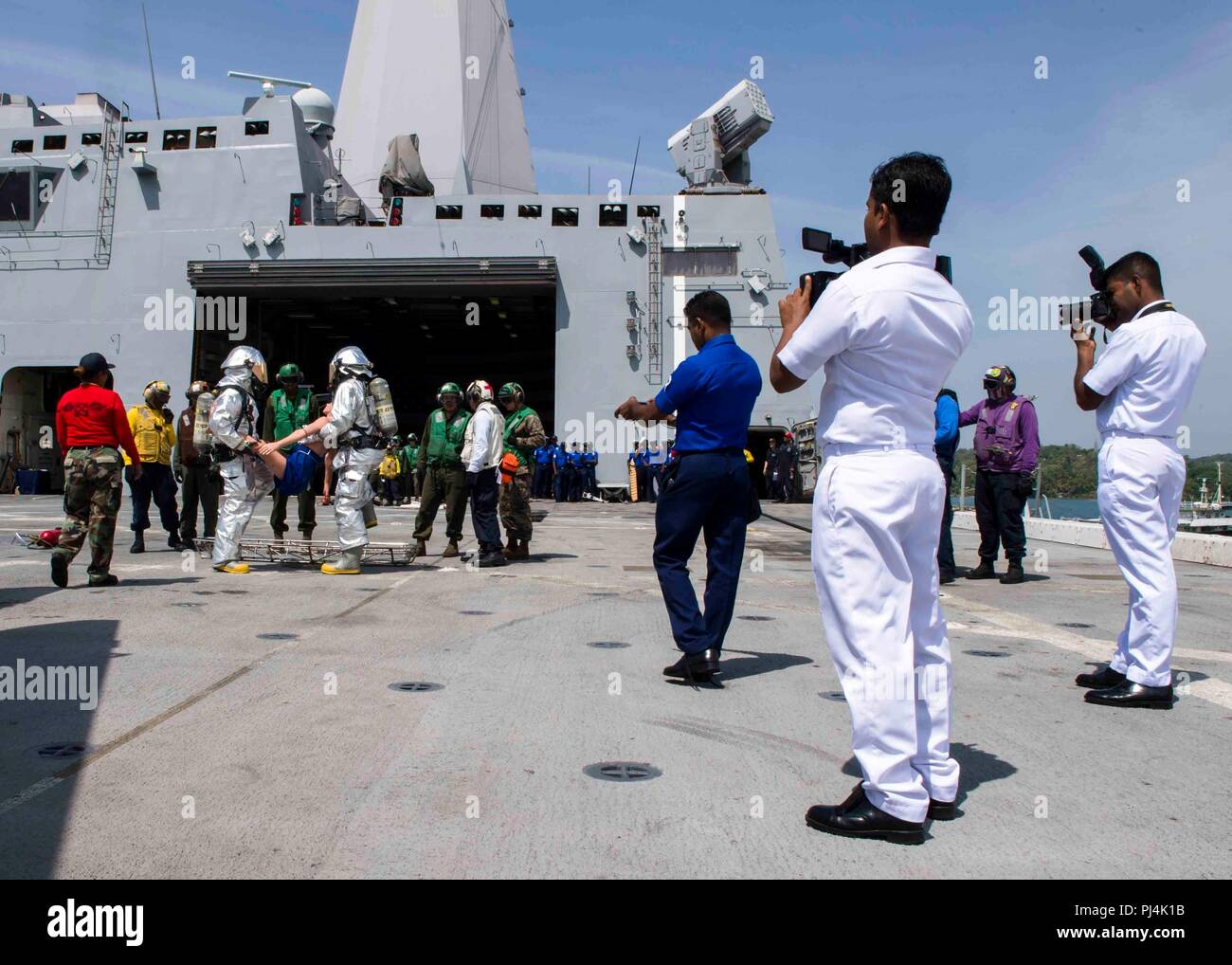 180826-N-PH222-0373 TRINCOMALEE, SRI LANKA (August 26, 2018) Sailors assigned to San Antonio-class amphibious transport dock USS Anchorage (LPD 23) and Marines assigned to the 13th Marine Expeditionary Unit (MEU) demonstrate emergency aircraft fire fighting techniques on the flight deck to the Sri Lanka navy sailors during a regularly scheduled deployment of the Essex Amphibious Ready Group (ARG) and the 13th MEU. Anchorage and the embarked Marines of the 13th MEU are conducting a theater security cooperation exercise with the Sri Lankan navy and Marines. Part of a growing U.S.-Sri Lanka naval - Stock Image