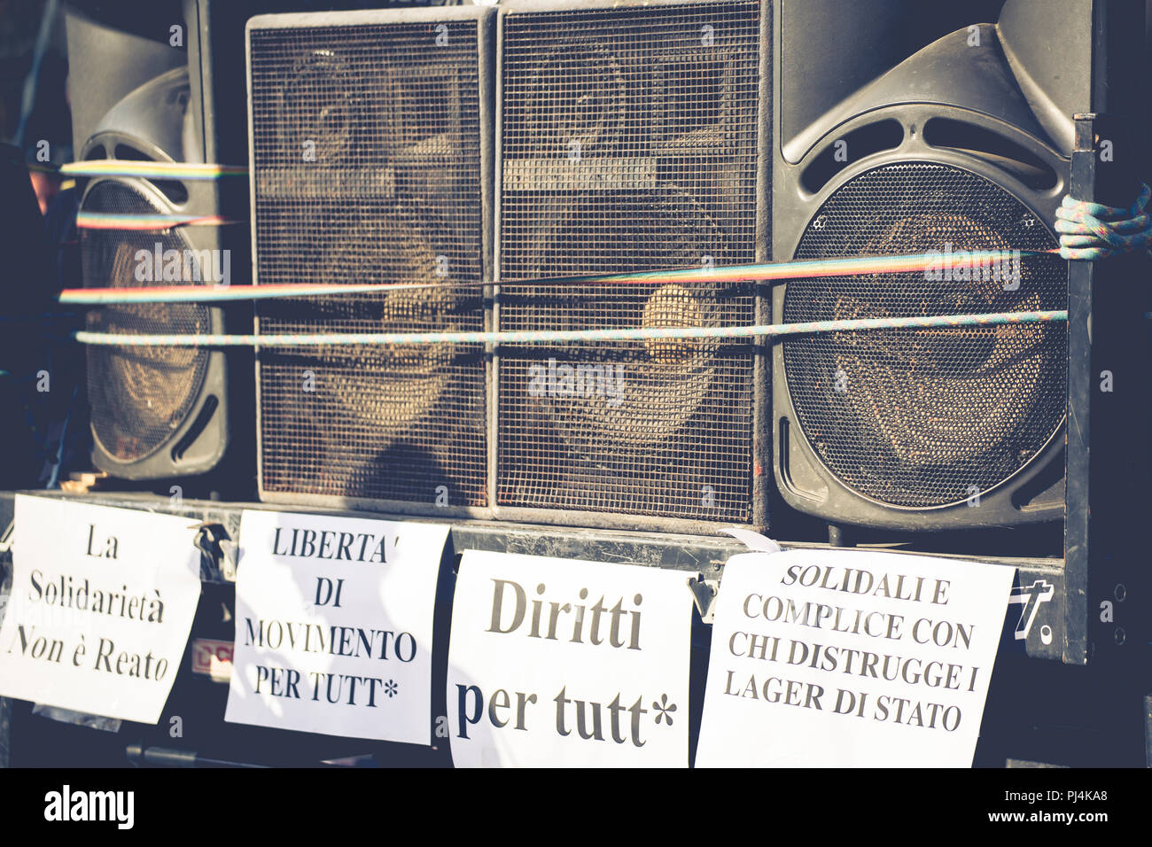 A wall of audio speakers and Italian anti-racist slogans - Stock Image