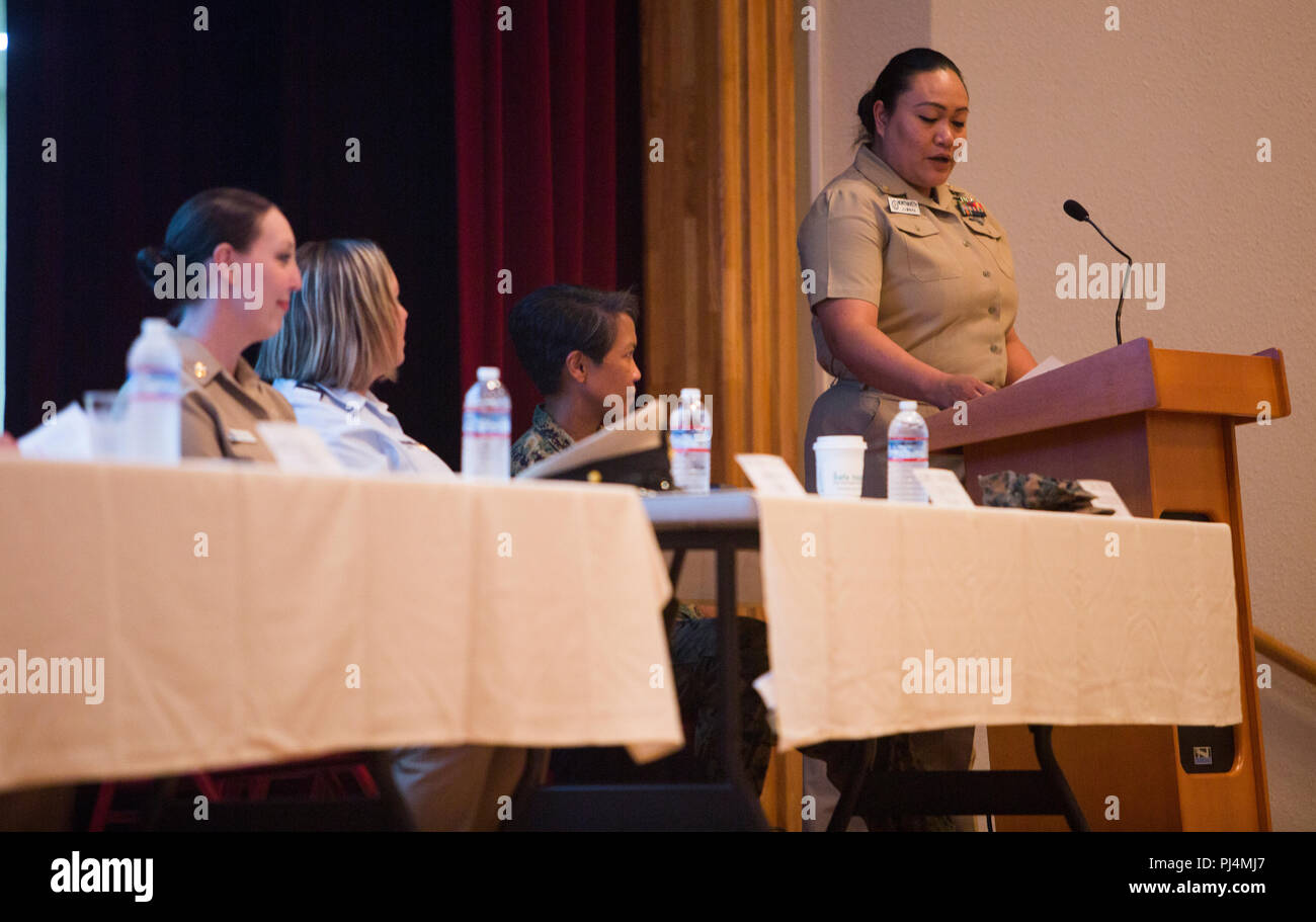 HMC Jane J. Nonthaveth, right, reads questions for a panel of active and retired servicewomen to answer during the Women's Symposium Aug. 30, 2018 at Camp Foster, Okinawa, Japan. The symposium promoted gender equality, empowerment and raised awareness of equal opportunity resources. Nonthaveth, the chief hospital corpsman with Naval Hospital Okinawa, is a native of Denver, Colorado. (U.S. Marine Corps photo by Cpl. Isabella Ortega) - Stock Image