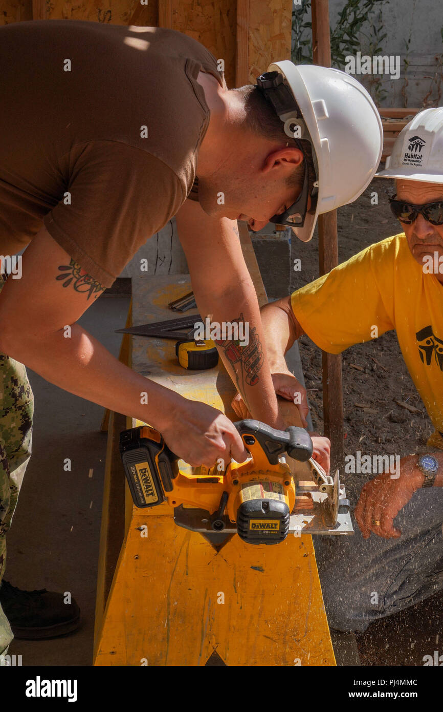 180829-N-FA490-1058 LOS ANGELES (Aug. 29, 2018) Yeoman 2nd Class Christian Laird, assigned to the Arleigh Burke-Class guided-missile destroyer USS DEWEY (DDG 105), saws a board during a Habitat for Humanity community relations project during Los Angeles Fleet Week (LAFW).  LAFW is an opportunity for the American public to meet their Navy, Marine Corps, and Coast Guard teams and experience America's sea services. During fleet week, service members participate in various community service events, showcase capabilities and equipment to the community, and enjoy the hospitality of Los Angeles and i - Stock Image