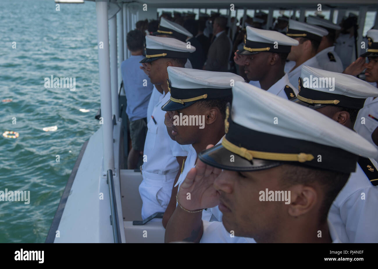 180831-N-AV243-0009 PEARL HARBOR (August 31, 2018) U.S. Navy Midshipmen honor the lives lost on December 7th, 1941 during a Pearl Harbor memorial boat tour.  The U.S. Navy Midshipmen visited the Pearl Harbor visitor center the day prior to their game against University of Hawaii's Rainbow Warriors on September 1, 2018. (U.S. Navy photo by Mass Communication Specialist 2nd Class Somers T. Steelman.) Stock Photo