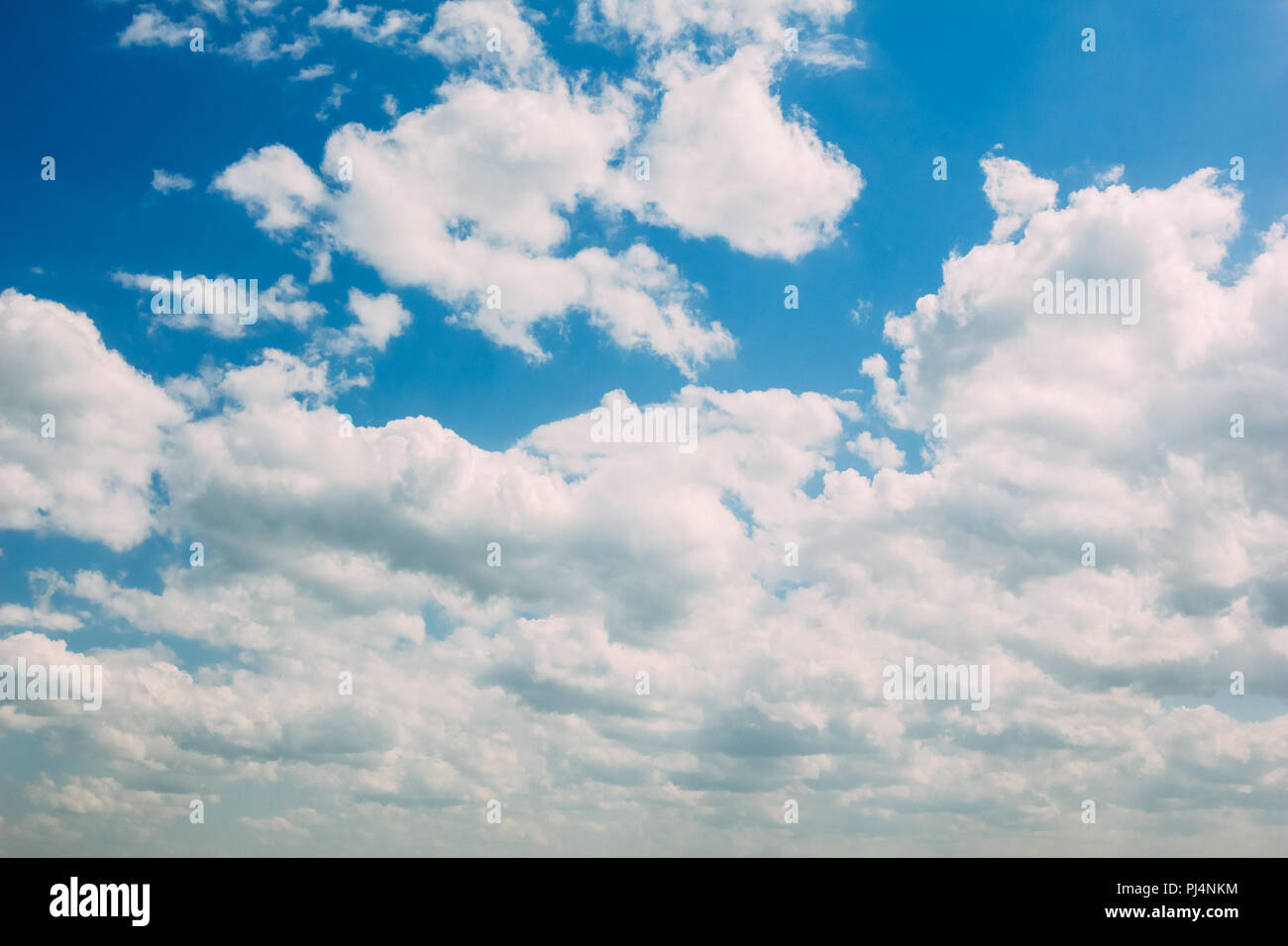 Cumulus white clouds on a blue summer sky background - Stock Image