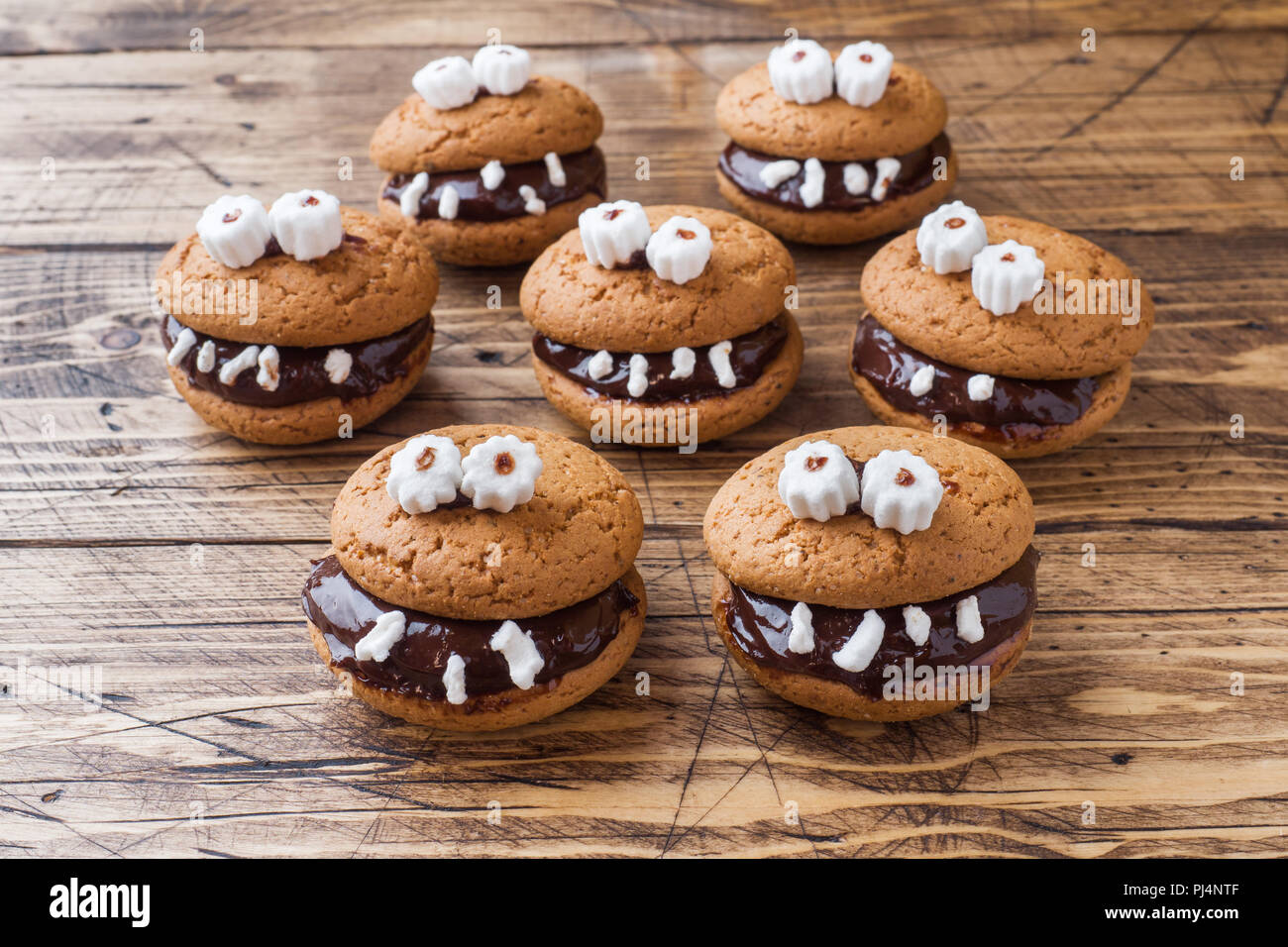 Cookies with chocolate paste in the form of monsters for Halloween. - Stock Image