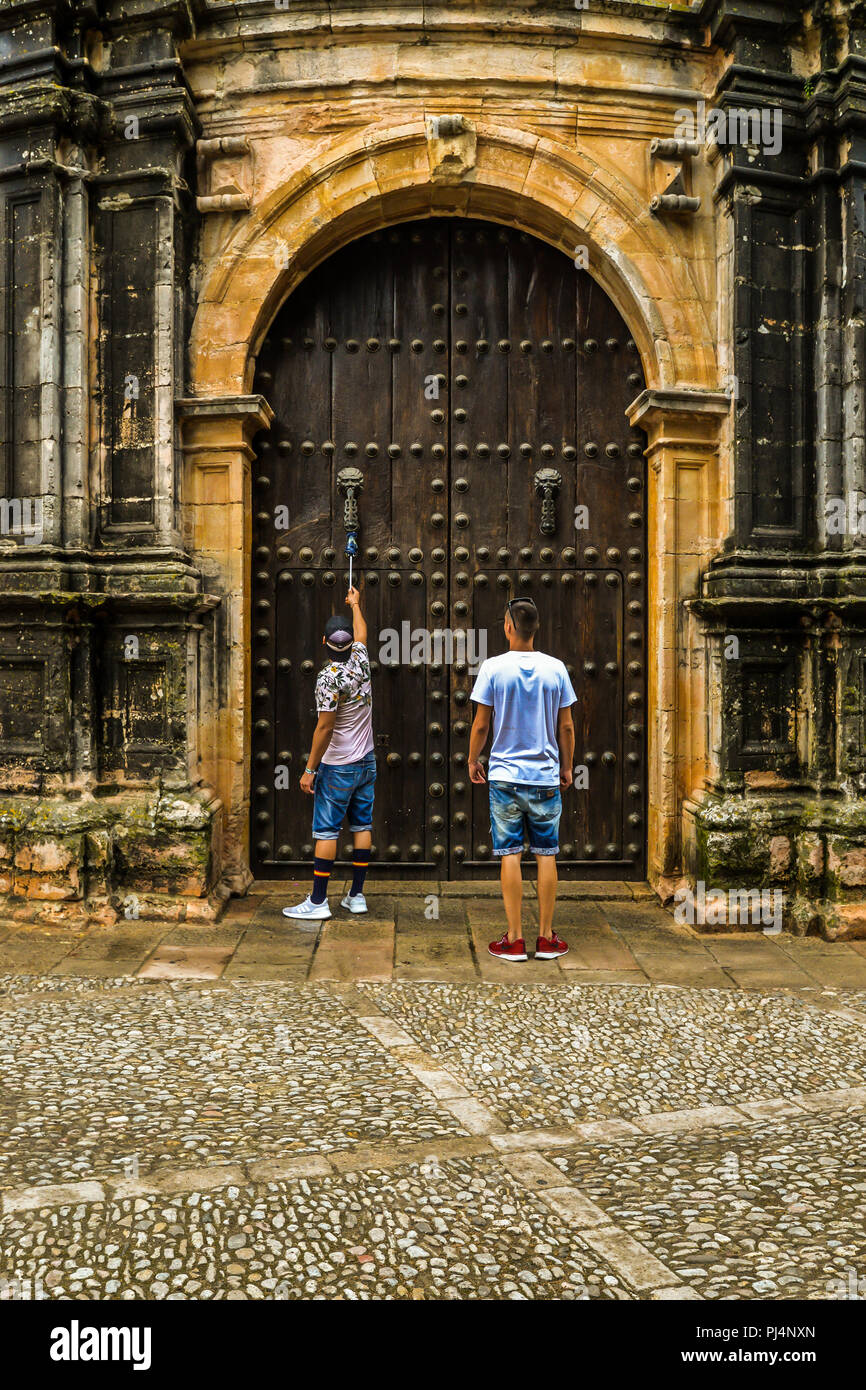 Two men knocking on an old door in Ronda - Stock Image