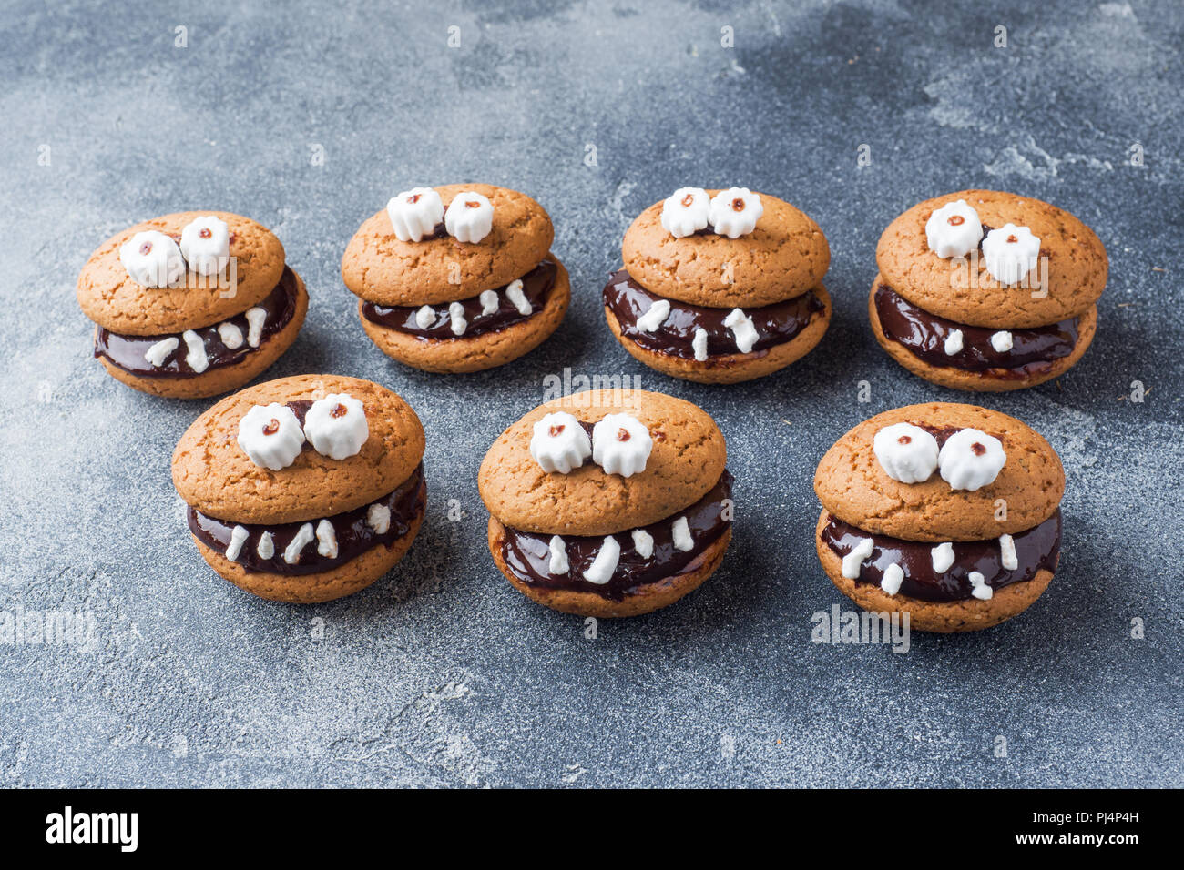 Cookies with chocolate paste in the form of monsters for Halloween. Stock Photo