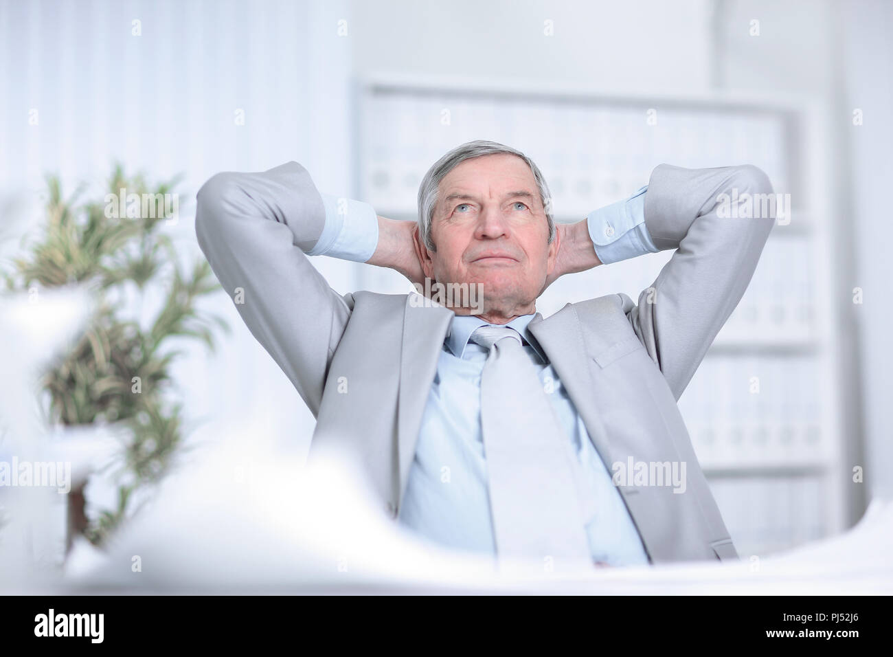 senior businessman dreaming of sitting at his Desk - Stock Image