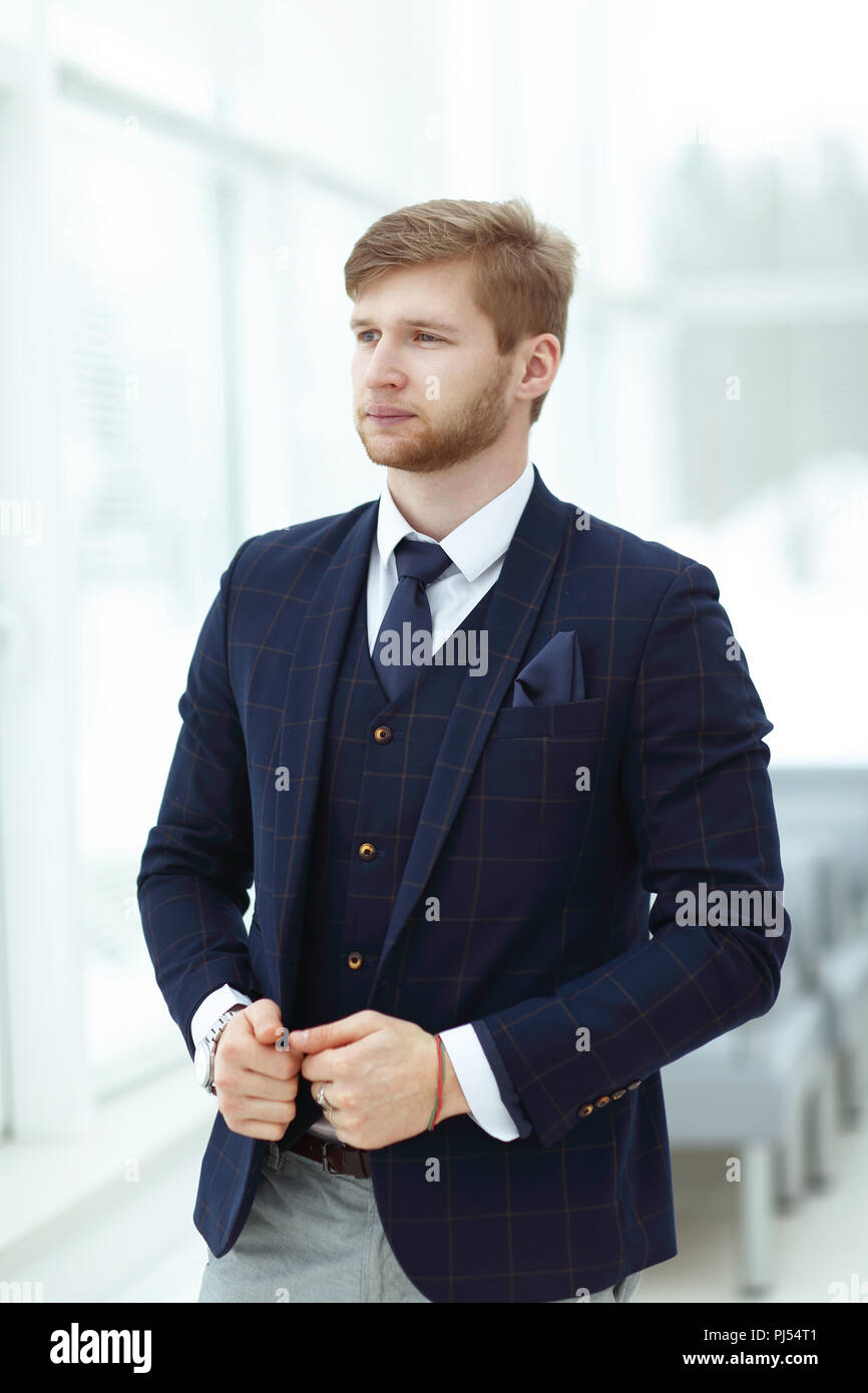pensive young businessman standing near the office window - Stock Image