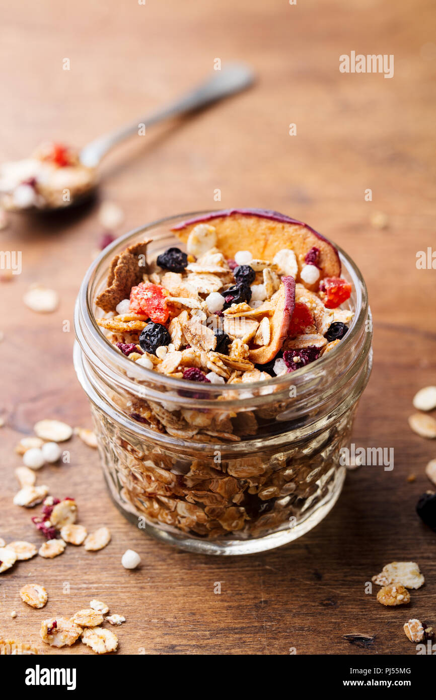 Granola, muesli in glass jar. Healthy breakfast. Organic oats with apples, berries, nuts. Copy space Stock Photo